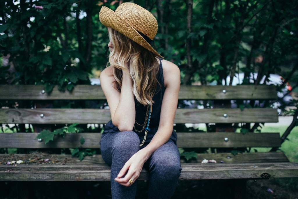 Woman sitting down on a bench to illustrate a blog post on the past continuous tense