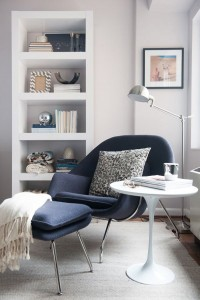 A photo of an armchair, table and bookshelves to illustrate a post about reading nooks
