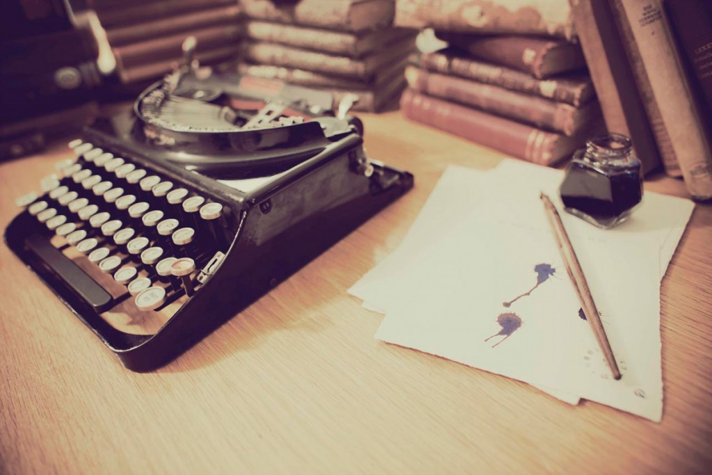 Photo of typewriter, ink bottle and books to illustrate a page about The Wordy House