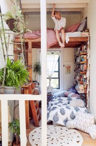 A photo of a cosy reading nook with quilts, cushions and books